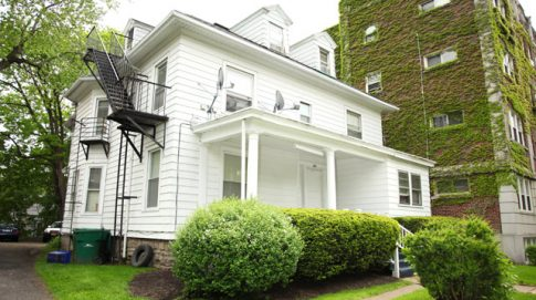A large open porch invites you into this bright multifamily home on Goodman Street in Rochester NY
